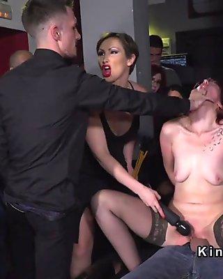 Hot redhead slave serves crowded bar